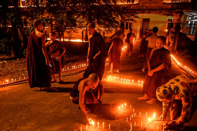Buddhist monks light candles at a monastery during the Thadingyut festival, which is held on the full moon day of the Burmese lunar month of Thadingyut, on the outskirts of Yangon on October 31, 2020. (Photo by Ye Aung Thu/AFP Photo)