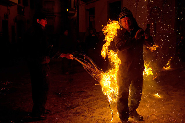 "A reveler is hit by a man waving a burning broom during the ""Los Escobazos"" Festivial on December 7, 2014 in Jarandilla de la Vera, Spain. The origin of this festival is unconfirmed. Most believe that it comes from when goat shepherds came down from the mountains to celebrate the Virgin's Conception Day (December 8th) the night before.  In order to see, they would light some branches of a brush called ""Escobones"" (Brooms). (Photo by Gonzalo Arroyo Moreno/Getty Images)"