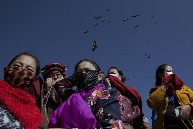 Ethnic Tibetan people protect themselves from the smell of decomposing bodies as vultures come from skies during a sky burial near the Larung valley located some 3700 to 4000 metres above the sea level in Sertar county, Garze Tibetan Autonomous Prefecture, Sichuan province, China October 31, 2015. (Photo by Damir Sagolj/Reuters)