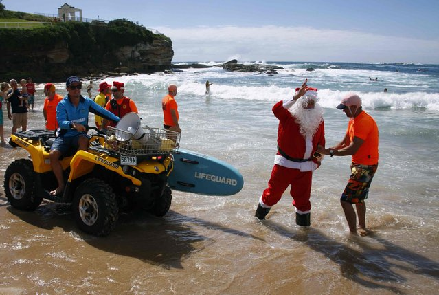 A man dressed as Santa Claus is assisted with having his pants adjusted after arriving in an inflatable rescue boat (IRB), as part of Christmas celebrations for the Coogee Surf Lifesaving Club, at Sydney's Coogee Beach December 14, 2014. (Photo by David Gray/Reuters)