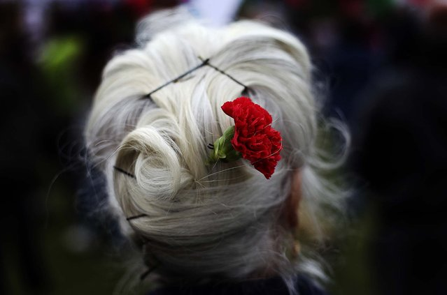 Maria Jose Duvalle, 75, wears a red carnation in her hair during the May Day workers march in Lisbon. The red carnation is the symbol of the April 25 leftist military uprising that restored democracy to Portugal after almost a half century of dictatorship. (Photo by Francisco Seco/Associated Press)