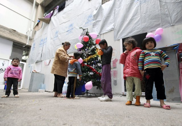 Displaced Iraqi Christian children who fled from Islamic State militants in Mosul,  gather around a Christmas tree at a mall still under construction, used as a refugee camp in Arbil December 24, 2014. (Photo by Azad Lashkari/Reuters)