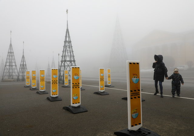 Pedestrians walk near a skating rink past signs requesting to wear protective face masks and to keep a social distance amid the coronavirus disease (COVID 19) outbreak, as heavy fog covers a square named after Soviet state founder Vladimir Lenin in Stavropol, Russia on December 1, 2020. (Photo by Eduard Korniyenko/Reuters)