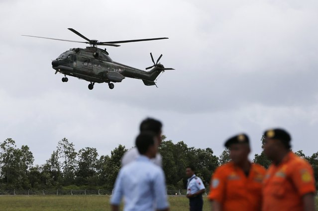 Search and rescue team members stand by as a helicopter prepares to land, during search operations for passengers onboard AirAsia flight QZ8501, at Iskandar airbase in Pangkalan Bun district, Indonesia, December 31, 2014. Indonesian rescuers believe they have found the wreck of the crashed AirAsia plane on the ocean floor off Borneo, after sonar detected a large, dark object beneath waters where debris and bodies were found floating. (Photo by Reuters/Beawiharta)