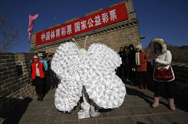 "Chinese artist Kong Ning wearing a costume symbolizing a butterfly, which is decorated with 365 masks on its wings to represent the number of days in a year, makes her way during her performance art at the Badaling section of the Great Wall on the outskirts of Beijing January 1, 2015. The banner refers to ""China Nationwide Sports Lottery"". (Photo by Kim Kyung-Hoon/Reuters)"