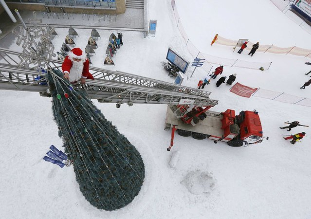 Firefighter Anton Shcherbakov, dressed as Santa Claus, stands on a fire-engine ladder as he decorates the top of a 14-metre-high Christmas tree ahead of the upcoming New Year and Christmas celebrations at the Bobrovy Log ski resort near Russia's Siberian city of Krasnoyarsk, December 29, 2014. (Photo by Ilya Naymushin/Reuters)