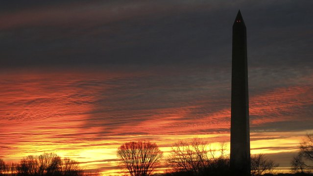 The sun sets behind the Washington Monument in Washington, January 4, 2015. (Photo by Jim Bourg/Reuters)