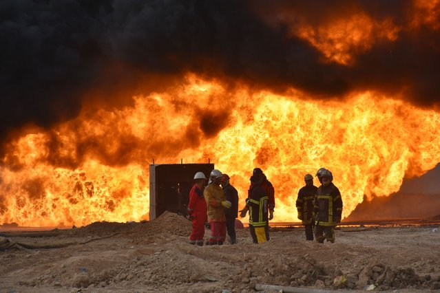 Firefighter teams conduct extinguish works after the Daesh carried out a bomb attack on wells in the Habbaza oil field in the Kirkuk province of Iraq on December 15, 2020. (Photo by Ali Makram Ghareeb/Anadolu Agency via Getty Images)