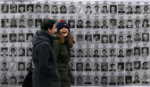 """A couple walks past a banner with pictures of Serbs, presumed killed by NATO and ethnic Albanian separatists in Kosovo, in front of the Serbia's war crimes court in Belgrade, Serbia, Thursday, January 8, 2015. Serbia's war crimes prosecutor Vladimir Vukcevic says his office has faced an orchestrated """"campaign of lynch"""" by war criminals and nationalists – including accusations of spying from the U.S. (Photo by Darko Vojinovic/AP Photo)"""