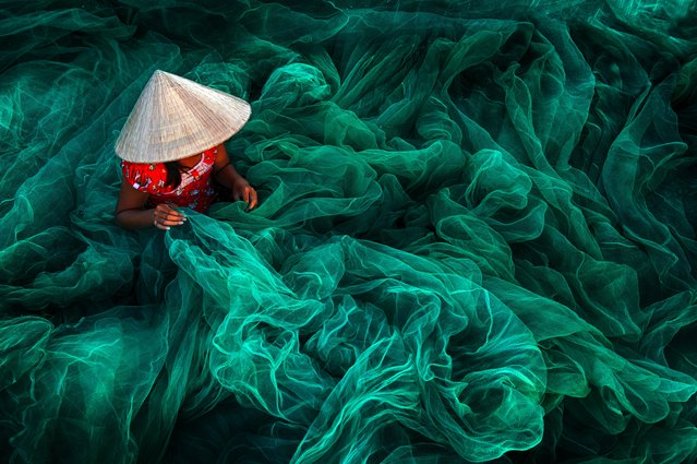 """Making fishing nets, Vietnam"". In the fishing village of Phan Rang in southern Vietnam, a woman creates a handmade fishing net. Winner: Open colour. (Photo by Danny Yen Sin Wong/SIPA Contest)"
