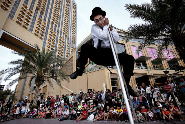 In this March 26, 2015 photo, visitors and tourists watch an entertainer perform during a street festival on the Marina waterfront in Dubai, United Arab Emirates. Dubai's rapid transformation from a desert outpost into one of the world's most architecturally stunning cities is mapped out in the  Marina. Dubai's year-round sunshine gives the Marina a summer-vibe throughout the winter months, when temperatures rarely drop below a comfortable 75 degrees Fahrenheit (24 Celsius) during the day. (Photo by Kamran Jebreili/AP Photo)