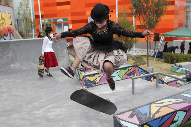 "Aide Choque, wearing a mask amid the COVID-19 pandemic, jumps with her skateboard during a youth talent show in La Paz, Bolivia, Wednesday, September 30, 2020. Young women called ""Skates Imillas"", using the Aymara word for girl Imilla, use traditional Indigenous clothing as a statement of pride of their Indigenous culture while playing riding their skateboards. (Photo by Juan Karita/AP Photo)"