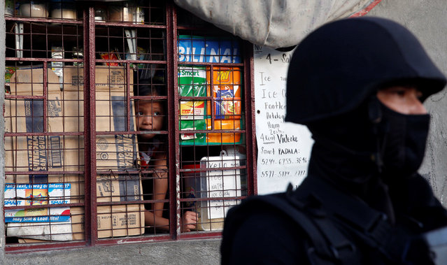 A girl looks out from the window during an anti-drug operation by the police, in Pasig, Metro Manila in the Philippines, November 9, 2016. (Photo by Erik De Castro/Reuters)