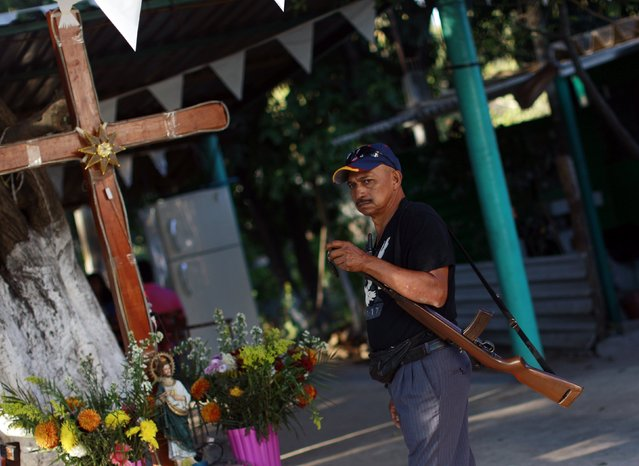 A member of the Community Police of the FUSDEG (United Front for the Security and Development of the State of Guerrero) stands in front of a cross and other mementos set up to mark the first anniversary of the force's operations in Ocotito, January 23, 2015. (Photo by Jorge Dan Lopez/Reuters)