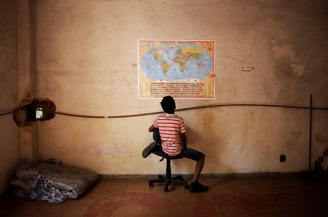 Wellington, 11, a relative of a member of Brazil's Movimento dos Sem-Teto (Roofless Movement), looks at a world map in a vacant apartment during the occupation of an empty building in downtown Sao Paulo, Brazil, November 10, 2016. (Photo by Nacho Doce/Reuters)