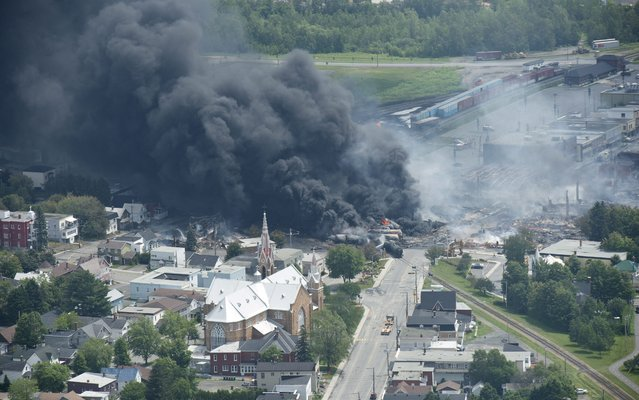 Smoke rises from railway cars that were carrying crude oil after derailing in downtown Lac Megantic, Quebec, Canada, Saturday, July 6, 2013. A large swath of Lac Megantic was destroyed Saturday after a train carrying crude oil derailed, sparking several explosions and forcing the evacuation of up to 1,000 people. (Photo by Paul Chiasson/AP Photo/The Canadian Press)