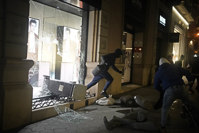 A person carrying goods runs from a smashed shop window during a protest condemning the arrest of rap singer Pablo Hasél in Barcelona, Spain, Saturday, February 20, 2021. (Photo by Joan Mateu/AP Photo)