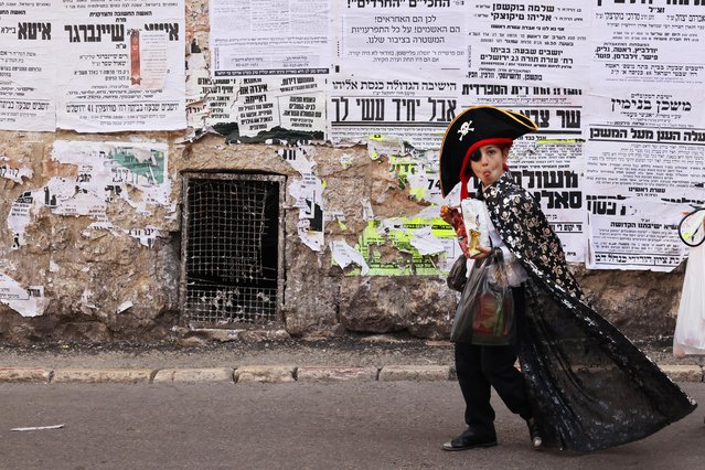 A boy wearing a dress-up costume to mark the upcoming Jewish holiday of Purim, which is a celebration of the Jews' salvation from genocide in ancient Persia, walks on a street in the ultra-Orthodox Jewish neighbourhood of Mea Shearim in Jerusalem on February 24, 2021. (Photo by Ammar Awad/Reuters)