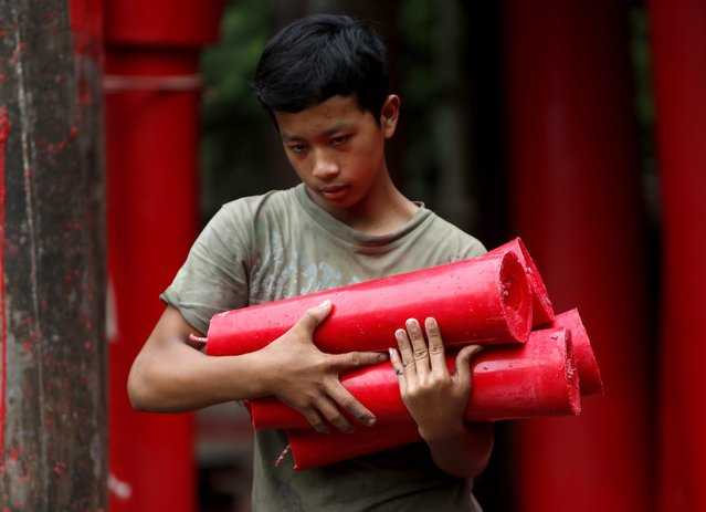 An Indonesian worker carries candles at a traditional Chinese candle maker for the upcoming Lunar New Year in Bogor, Indonesia, 27 January  2015. (Photo by Adi Weda/EPA)