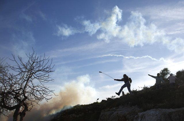 A Palestinian protester uses a slingshot to throw stones at Israeli troops during clashes near Israel's Ofer Prison, near the West Bank city of Ramallah January 23, 2015. (Photo by Mohamad Torokman/Reuters)