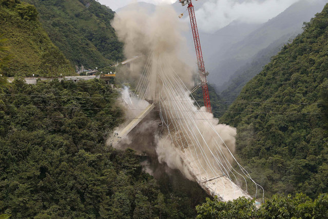 In this July 11, 2018 photo, a partially-built suspension bridge is demolished by engineers in Chirajara, Colombia. One part of the bridge collapsed in January during its construction, killing at least nine workers. (Photo by Fernando Vergara/AP Photo)