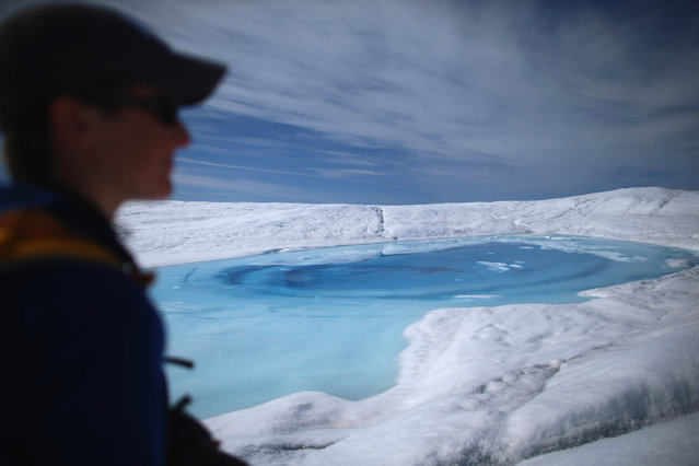 Laura Stevens, graduate student from the Massachusetts Institute of Technology and Woods Hole Oceanographic Institution, walks past a meltwater lake on July 16, 2013. She along with a group of scientists closely monitor the evolution of the surface lakes and the motion of the surrounding ice sheet. (Photo by Joe Raedle/Getty Images via The Atlantic)