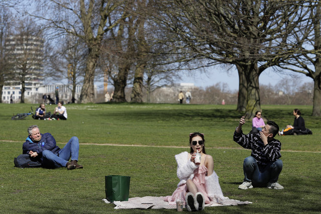 People picnic in Hyde Park, as lockdown easing begins in London, Monday, March 29, 2021. England is embarking on a major easing of its latest coronavirus lockdown that came into force at the start of the year, with families and friends able to meet up in outdoor spaces and many outdoor sports are permitted once again. (Photo by Kirsty Wigglesworth/AP Photo)