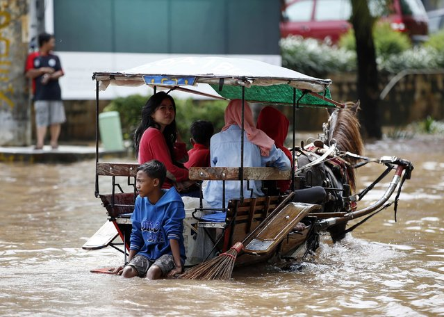 People ride in a horse-drawn carriage down a flooded street after continuous heavy seasonal rains inundated many parts of Jakarta February 10, 2015. (Photo by Darren Whiteside/Reuters)