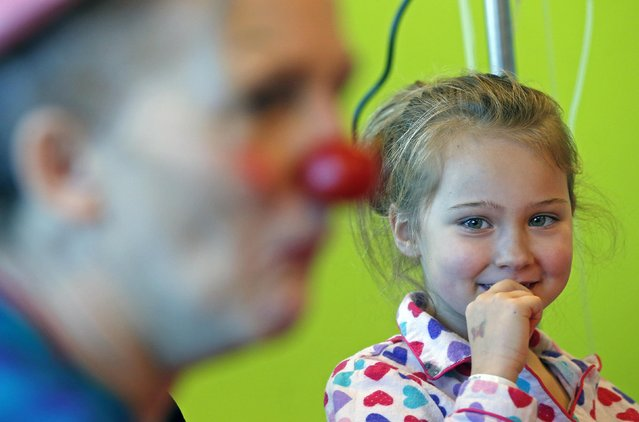 Malena, 7, looks at Belgian clown Lili Bellule at the pediatric department of the Hopital Erasme at the Universite Libre de Bruxelles (ULB), in Brussels January 27, 2015. The hospital offers performances by musicians and clowns as a form of therapy to help children cope with dealing with the stress and fear caused by hospitalization. (Photo by Yves Herman/Reuters)