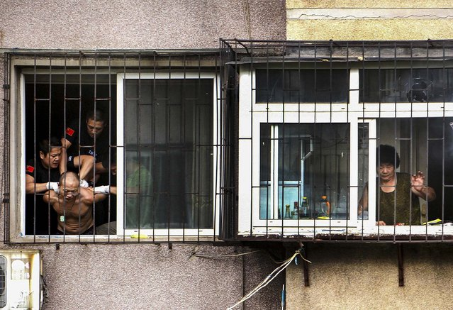 Police grab a man after he threatened to cut himself in Anshan, Liaoning province. The man held his mother captive in his apartment before climbing out of the window and threatening to harm himself. (Photo by Reuters)