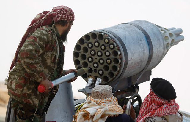 Rebel fighters load a UB-32 rocket pod mounted on a pickup truck, in the front line along the western entrance of Ajdabiya, on April 19, 2013. (Photo by Amr Abdallah Dalsh/Reuters)