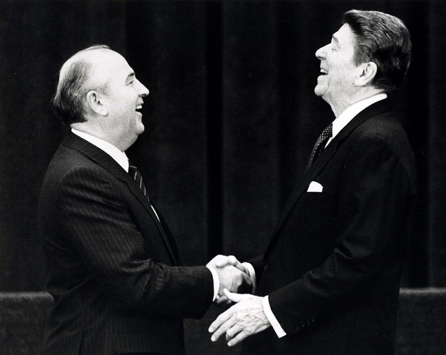 U.S. President Ronald Reagan (R) shakes hands at his first meeting with Soviet leader Mikhail Gorbachev to sign an arms treaty in Geneva, in this November 19, 1985 file photo. The two leaders met for the first time to hold talks on international diplomatic relations and the arms race. (Photo by Reuters/Stringer)
