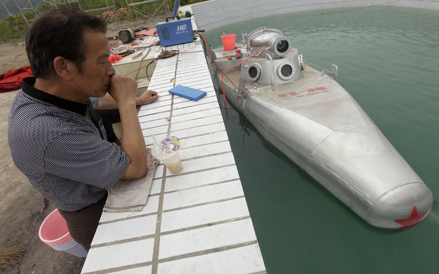 An engineer working for Zhang Wuyi looks at a double-seater submarine during a test operation at an artificial pool near a shipyard in Wuhan, Hubei province May 7, 2012. (Photo by Reuters/Stringer)