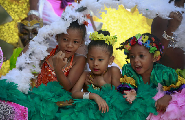 Three little girls ride on a float during Carnival celebrations in Panama City, Monday, February 16, 2015. (Photo by Arnulfo Franco/AP Photo)