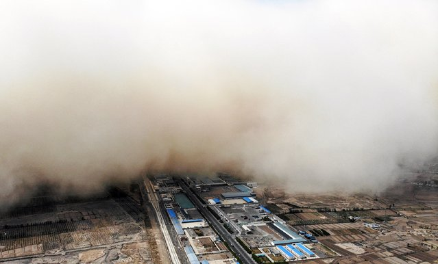 This aerial photo taken on April 25, 2021 shows a sandstorm engulfing a village in Linze county, in the city of Zhangye in China's northwestern Gansu province. (Photo by AFP Photo/China Stringer Network)