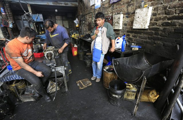 Workers in an engine workshop use an old oil barrel to collect waste oil from the engines they repair in Bogota February 14, 2015. (Photo by Jose Miguel Gomez/Reuters)