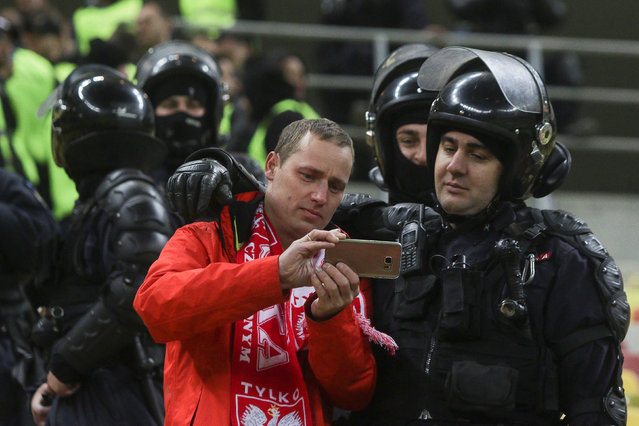 Football Soccer, Romania vs Poland, World Cup 2018 Qualifiers, National Arena Stadium, Bucharest, Romania on November 11, 2016. A Polish fans snaps a selfie with a Romanian gendarme at the end of the match. (Photo by Octav Ganea/Reuters/Inquam Photos)