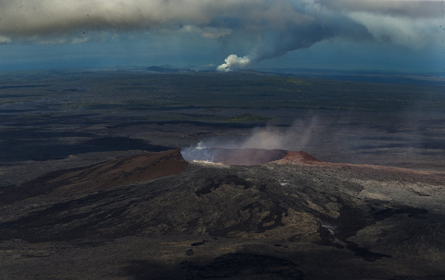 In this June 6, 2018 file photo, the caldera on the Kilauea Volcano emits a small amount of steam with the lower east rift zone eruption lava access point in Kapoho putting out much more in the distance continues in Pahoa, Hawaii. (Photo by L.E. Baskow/AP Photo)