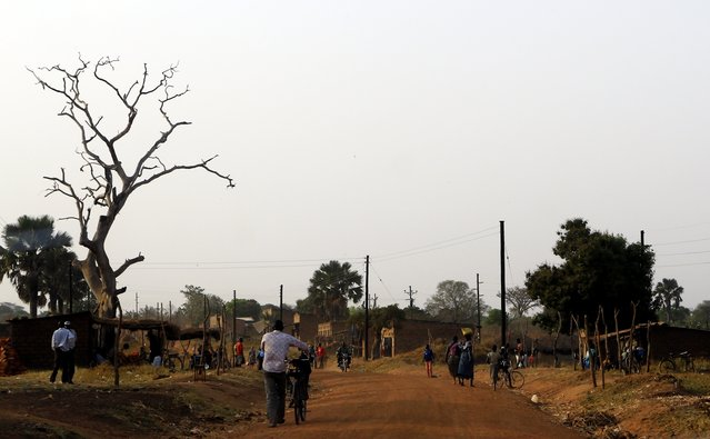People walk on a dusty road in the main commercial area of Odek village, north of Uganda capital Kampala February 14, 2015. (Photo by James Akena/Reuters)