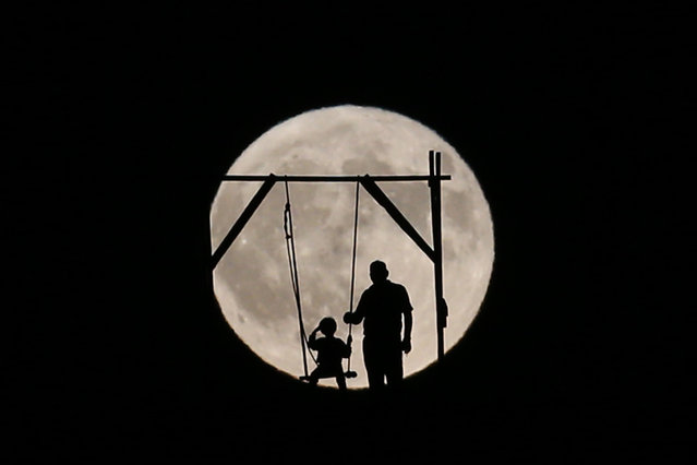 Silhouette of a man pushing a child on a swing in front of a full moon in Kayseri, Turkey on August 26, 2018. (Photo by Sercan Kucuksahin/Anadolu Agency/Getty Images)