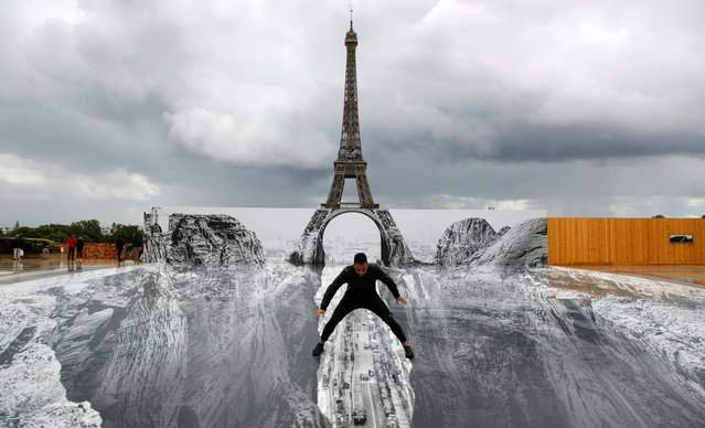 A man poses on a giant artwork by French artist JR installed on the Trocadero square in front of the Eiffel Tower in Paris, France, May 19, 2021. (Photo by Sarah Meyssonnier/Reuters)