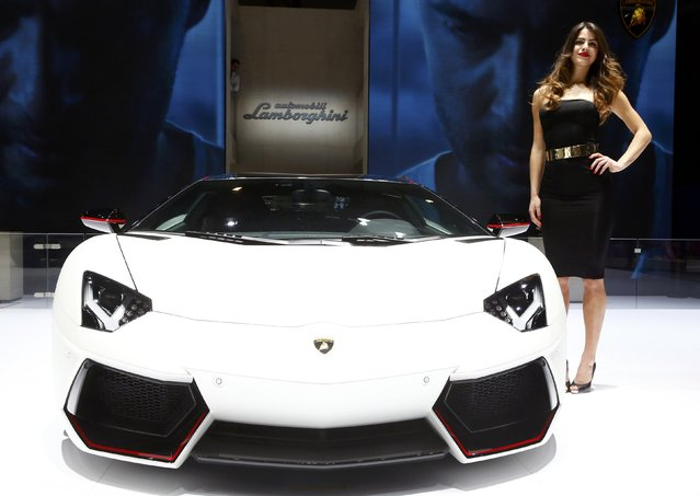 A model poses next to a Lamborghini Aventador LP 700-4 during the second press day ahead of the 85th International Motor Show in Geneva March 4, 2015.  REUTERS/Arnd Wiegmann