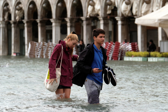 A couple walk on a catwalk in a flooded Saint Mark Square during a period of seasonal high water in Venice on October 29, 2018. (Photo by Manuel Silvestri/Reuters)