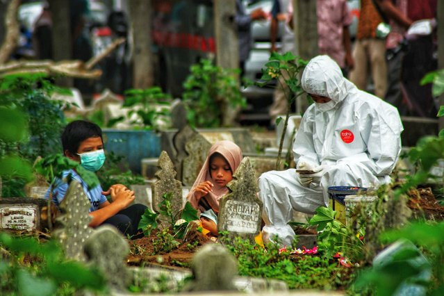 A family member in personal protective equipment (PPE) suit together with two children pray by the grave of a Covid-19 coronavirus victim who was just buried, as family members defying health protocols gather nearby at a cemetery in Lhokseumawe, Aceh on May 18, 2021. (Photo by Azwar Ipank/AFP Photo)