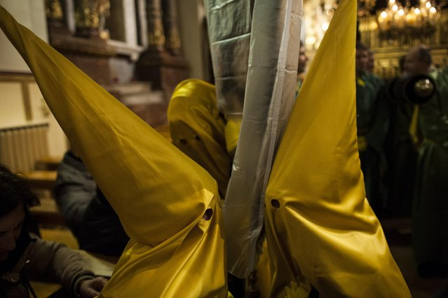 "Young masked penitents take part in the procession of the ""La Dolorosa"" brotherhood, in Pamplona northern Spain, Friday, March 20, 2015, a large week prior to celebrate Holy Week. (Photo by Alvaro Barrientos/AP Photo)"