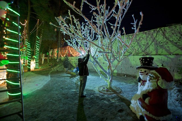A man decorates a tree for Christmas in a Christian neighborhood of Islamabad, Pakistan, Saturday, December 24, 2016. (Photo by B.K. Bangash/AP Photo)