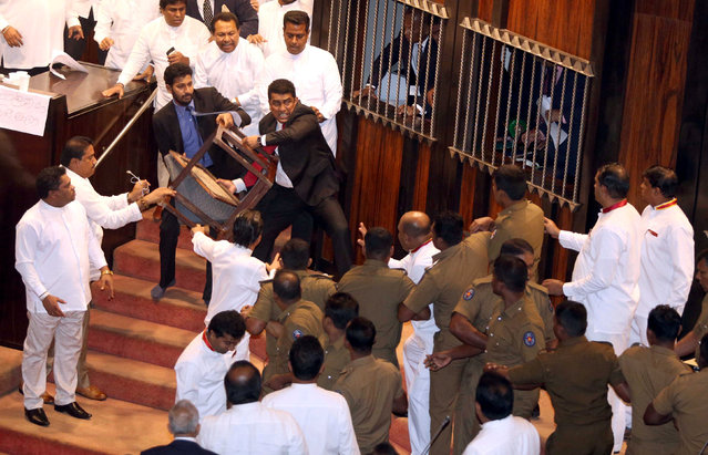 Parliament member Johnston Fernando who is backing newly appointed Prime Minister Mahinda Rajapaksa throws a chair at police who are there to protect parliament speaker Karu Jayasuriya (not pictured) during a parliament session in Colombo, Sri Lanka November 16, 2018. (Photo by Reuters/Stringer)