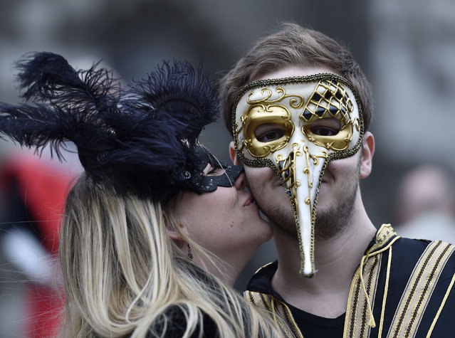 A reveller gets a kiss during the start of the street carnival in Cologne, Germany, on Thursday, February 4, 2016. (Photo by Martin Meissner/AP Photo)