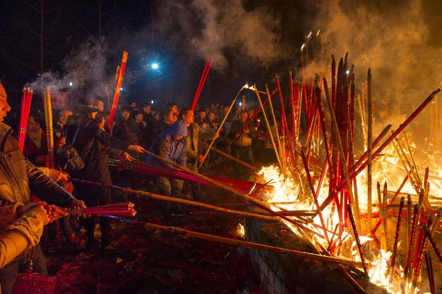 People burn incense as they pray for good fortune at the beginning of the Chinese Lunar New Year, at Wuyou temple in Leshan, Sichuan province, February 8, 2016. (Photo by Reuters/Stringer)