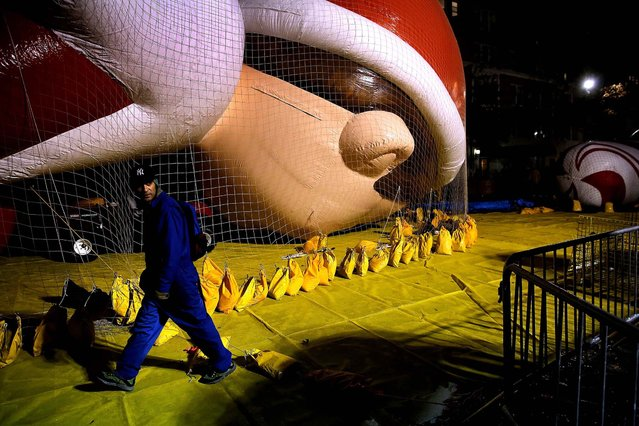 Workers prepare giant balloons on Wednesday night for Thursday's 87th annual Macy's Thanksgiving Day Parade in New York City. (Photo by John Moore/Getty Images)